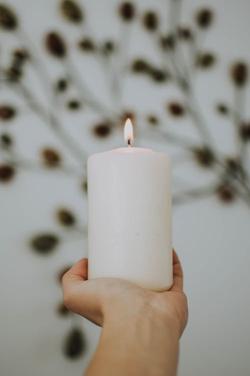 Photo of Hand Holding Lit White Pillar Candle