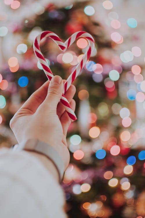 Photo of Person Holding Heart Shaped Candy Cane