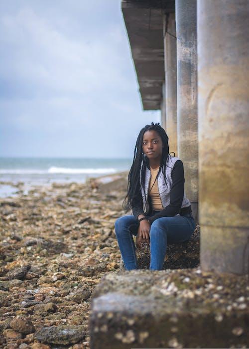 Woman Sitting on Concrete Bridge Support