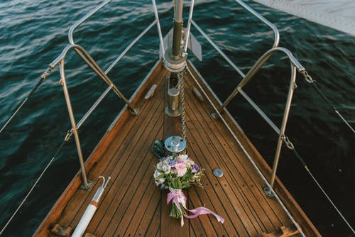 White and Purple Flowers Bouquet on Brown Wooden Boat Ground on Body of Water