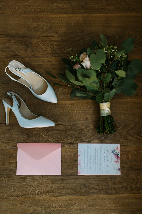 Pair Of White Leather Pointed-toe Slingback Shoes Beside Bouquet Of Flowers