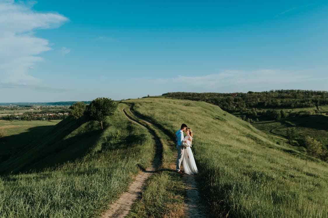 Man and Woman Standing Near Green Grass