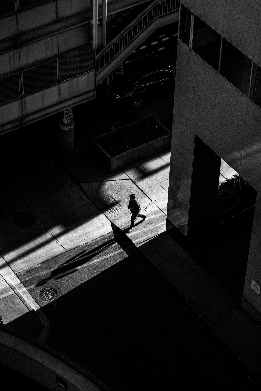 Grayscale Photo of Man Walking on Street Near Buildings