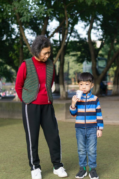 Toddler Boy Standing Beside Woman