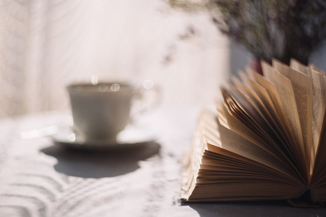 Tilt Lens Photography of Open Book With Ceramic Cup in Saucer