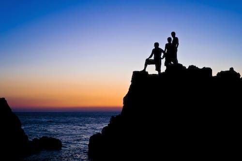 Безкоштовне стокове фото на тему «Захід сонця, люди, море, плавати»