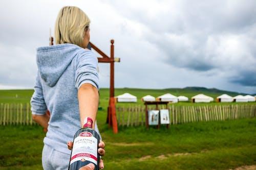 Woman Grabbing Glass Bottle Near Field