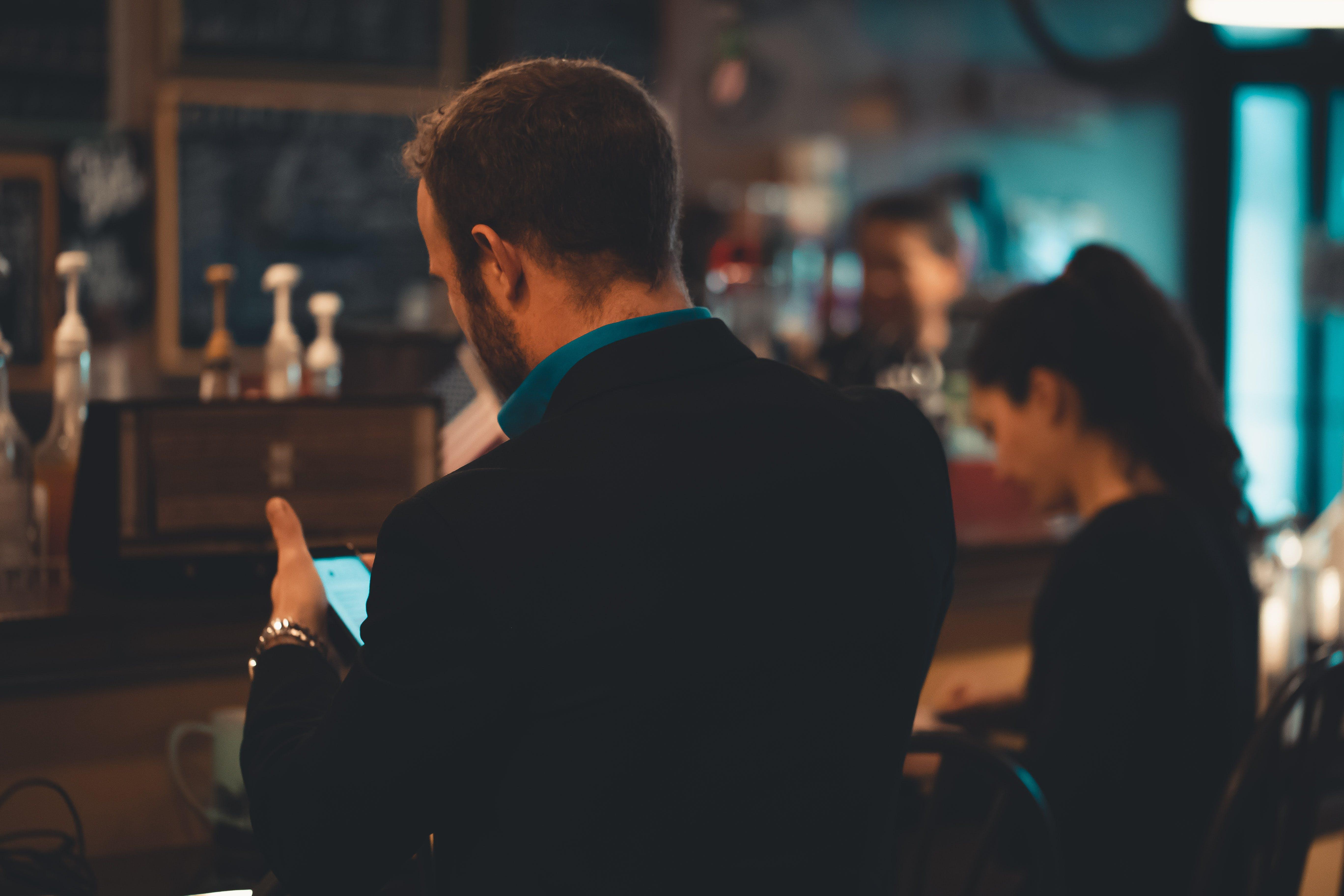 Man in Black Suit Jacket Using Smartphone Indoors in Tilt Shift Photography