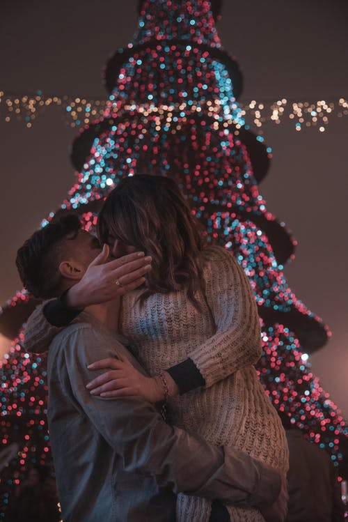 Photo of Couple Kissing In Front Of Christmas Tree