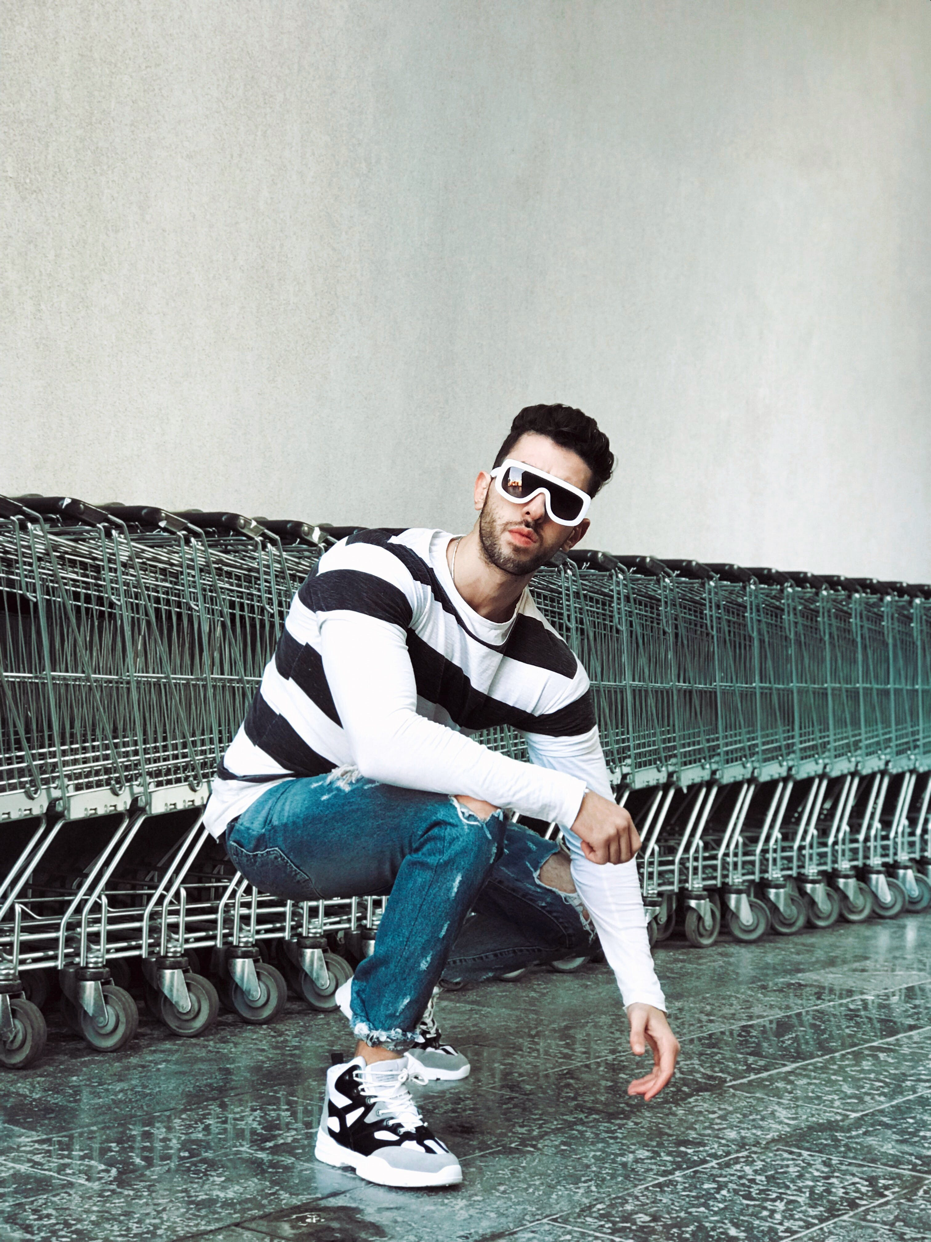 Photo of Man Squat Position in Front of Shopping Carts