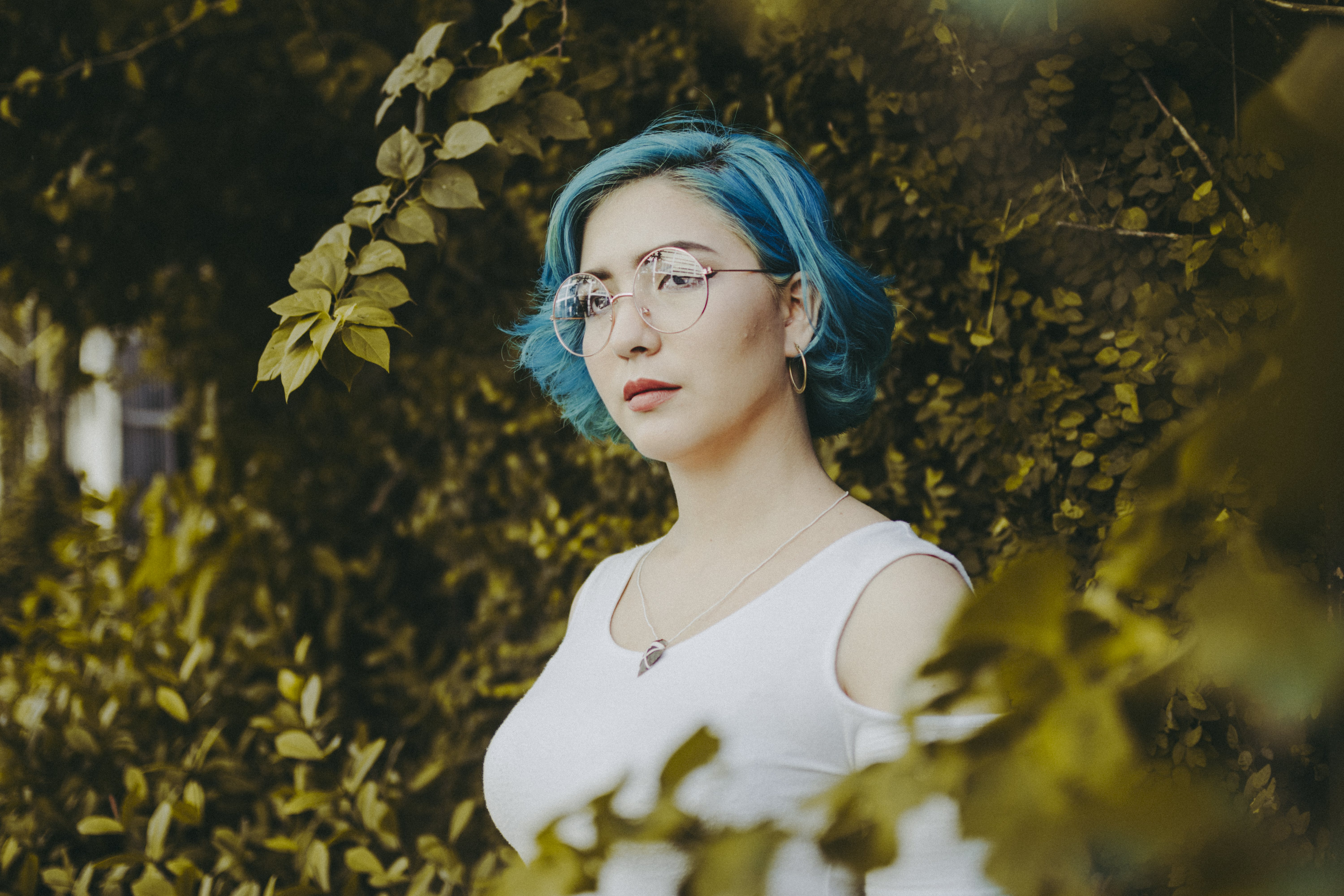Blue-haired Woman Surrounded by Green-leafed Plants