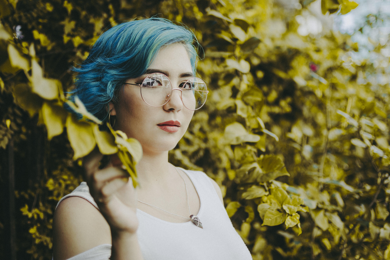 Woman Holding Leaf While Wearing Eyeglasses