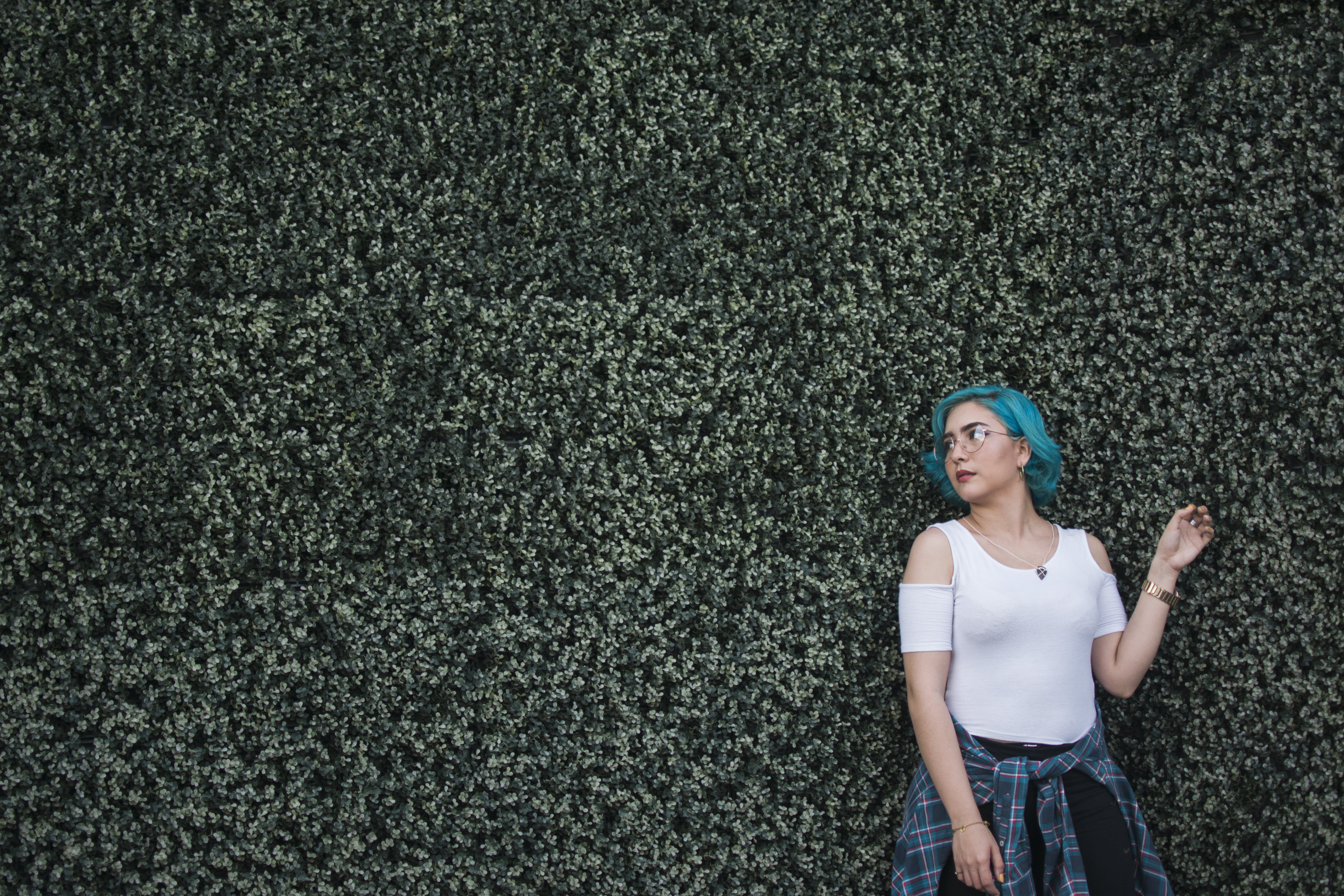 Woman in White Top Standing in Front of Green Leafed Hedge Wall