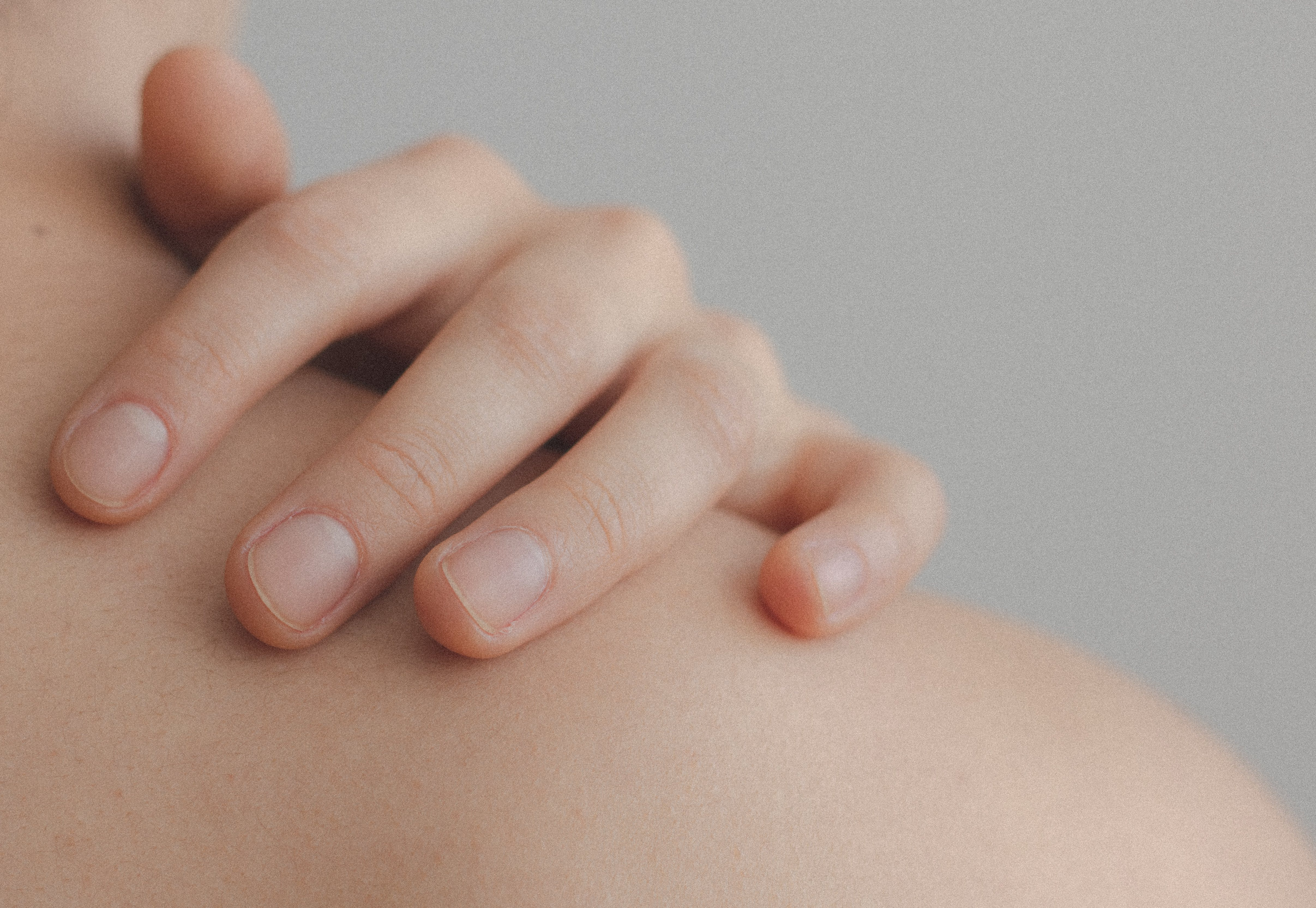Close-up Photo of Person Touching their Shoulder