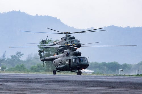 Military commando helicopters landing on asphalt ground