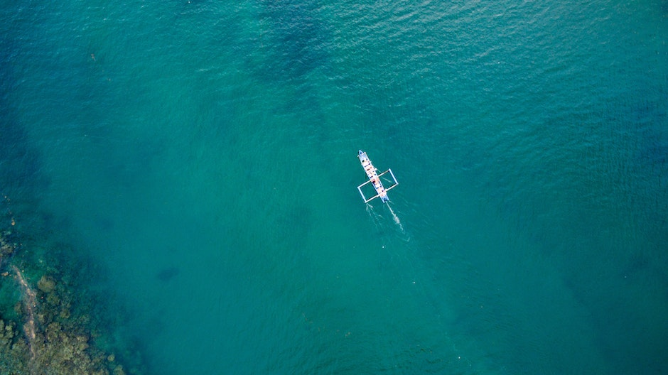 White Boat on Green Body of Water during Daytime