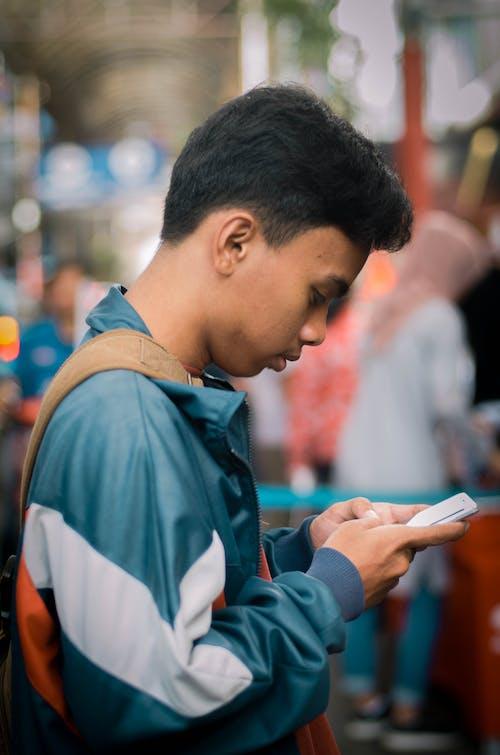 Photographie De Mise Au Point Sélective De L'homme Tenant Le Smartphone