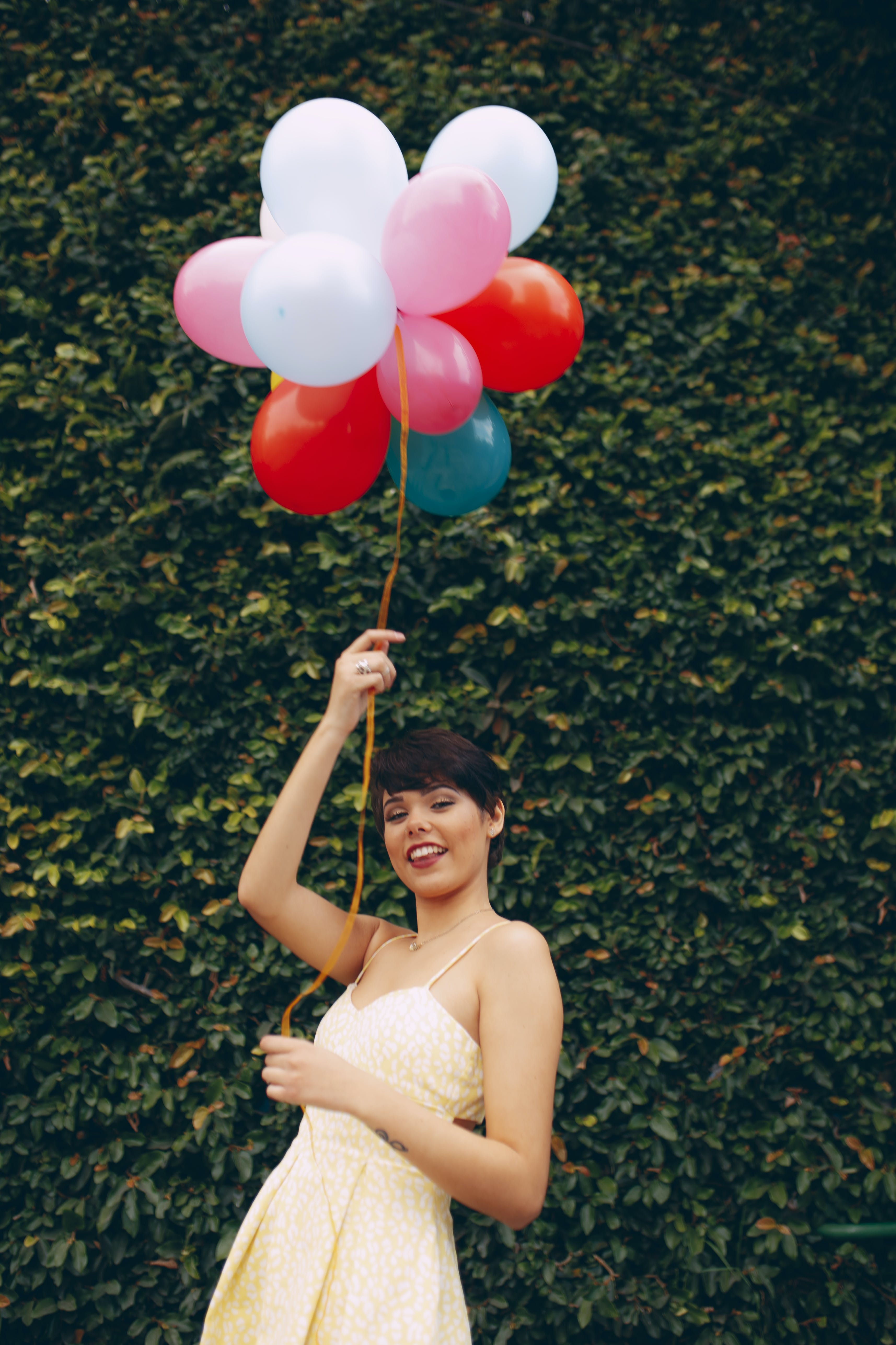Photo of Smiling Woman Holding Balloons