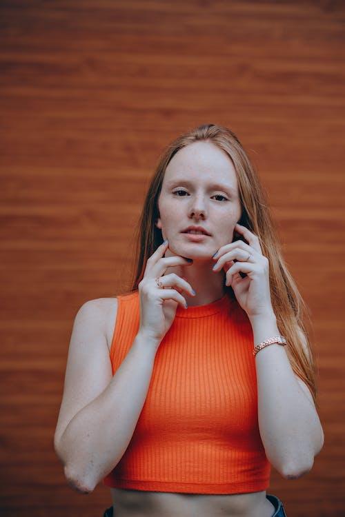 Photo of Woman Wearing Orange Sleeveless Crop Top