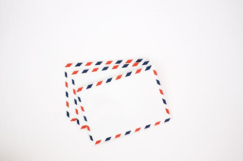 Top view set of white envelops with striped red and blue edges placed on plain white background