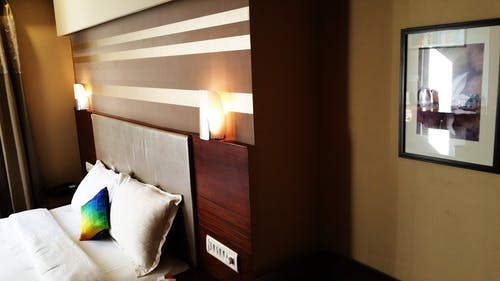 Empty Bed With Wooden Headboard and Lamps