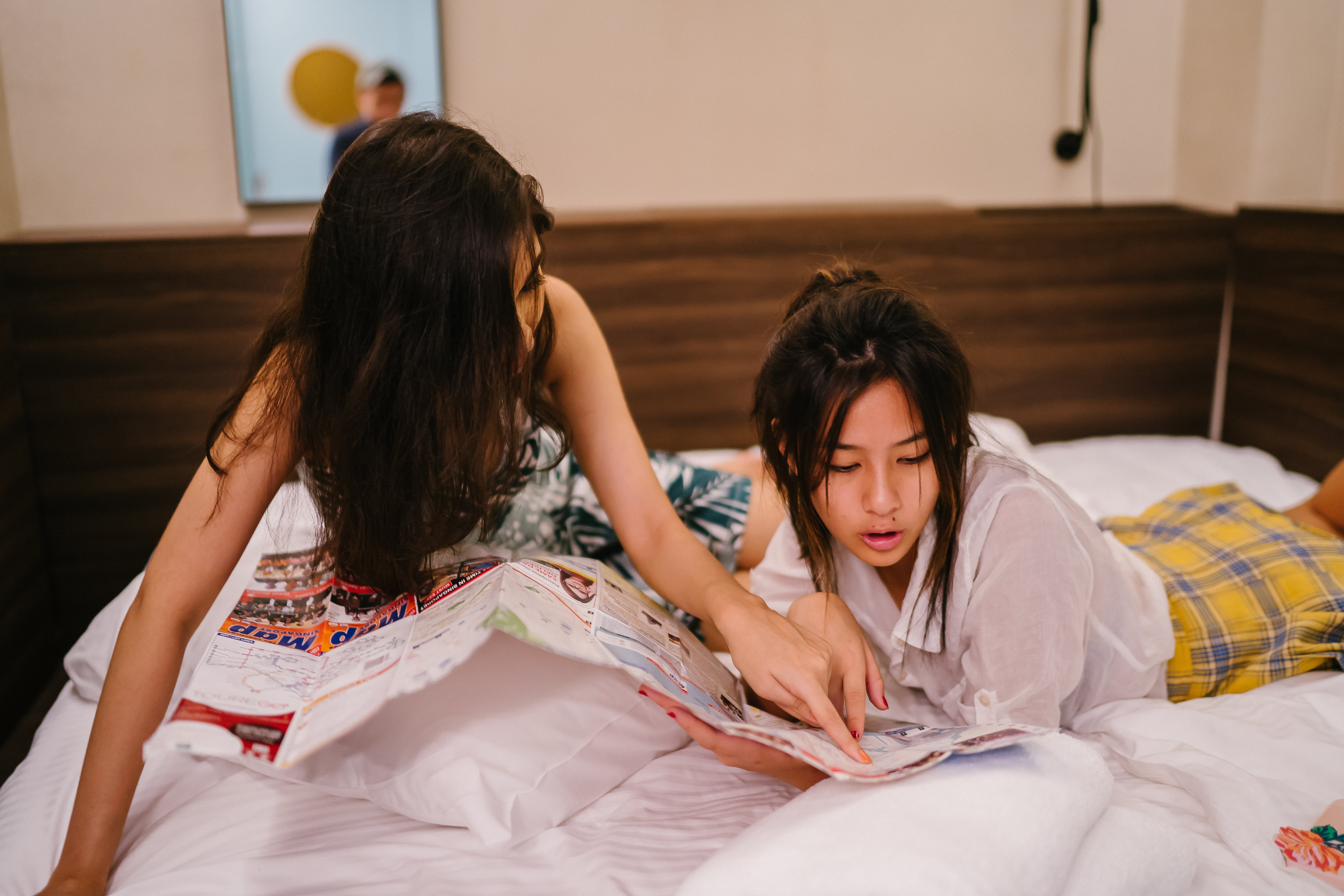 Two Women Laying On Bed While Looking At Paper
