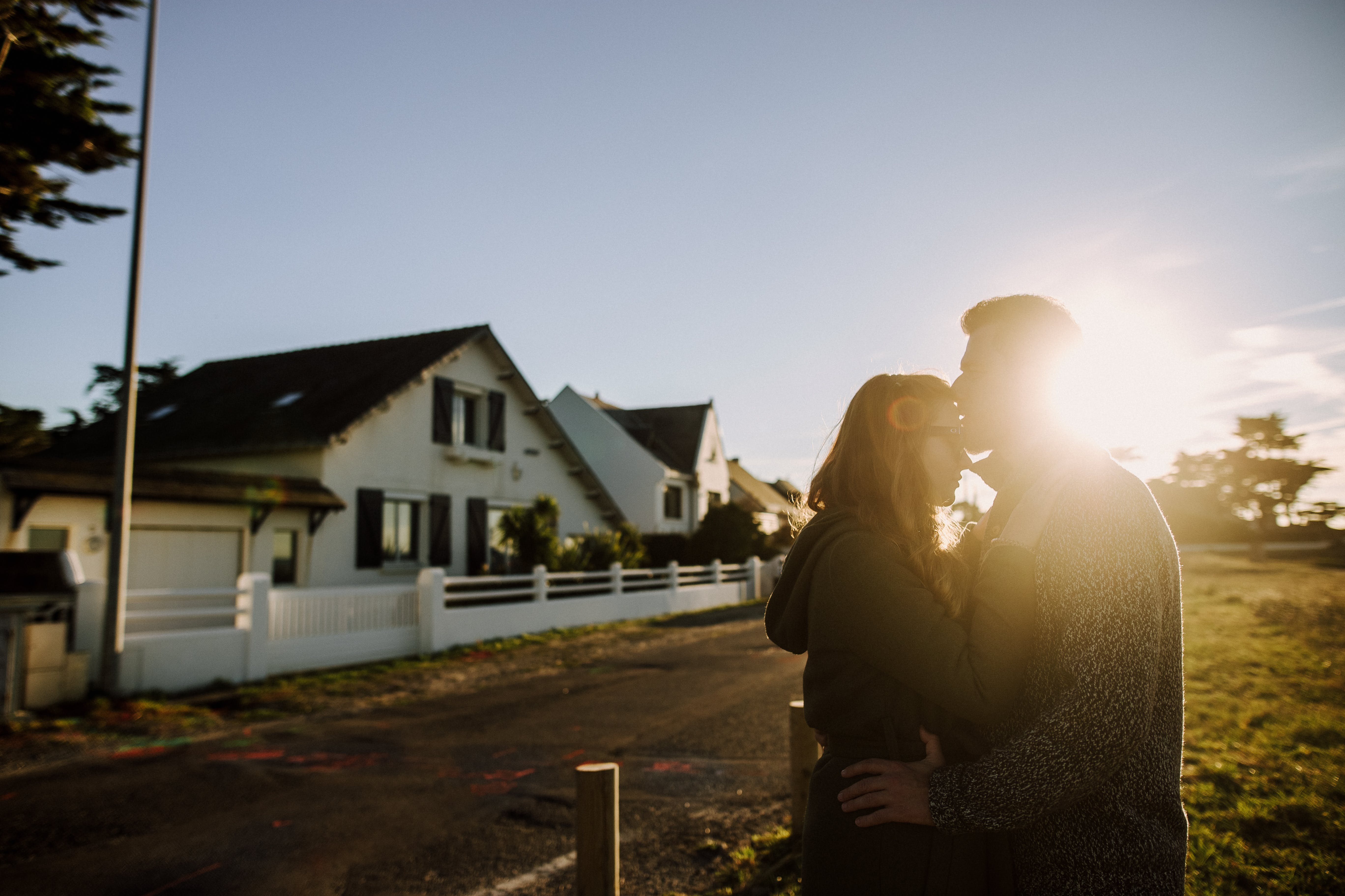 Man Kissing Woman's Forehead Under Sunset