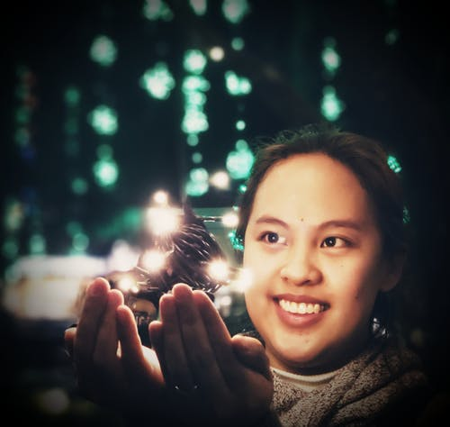 Photo of Woman Near Christmas Lights