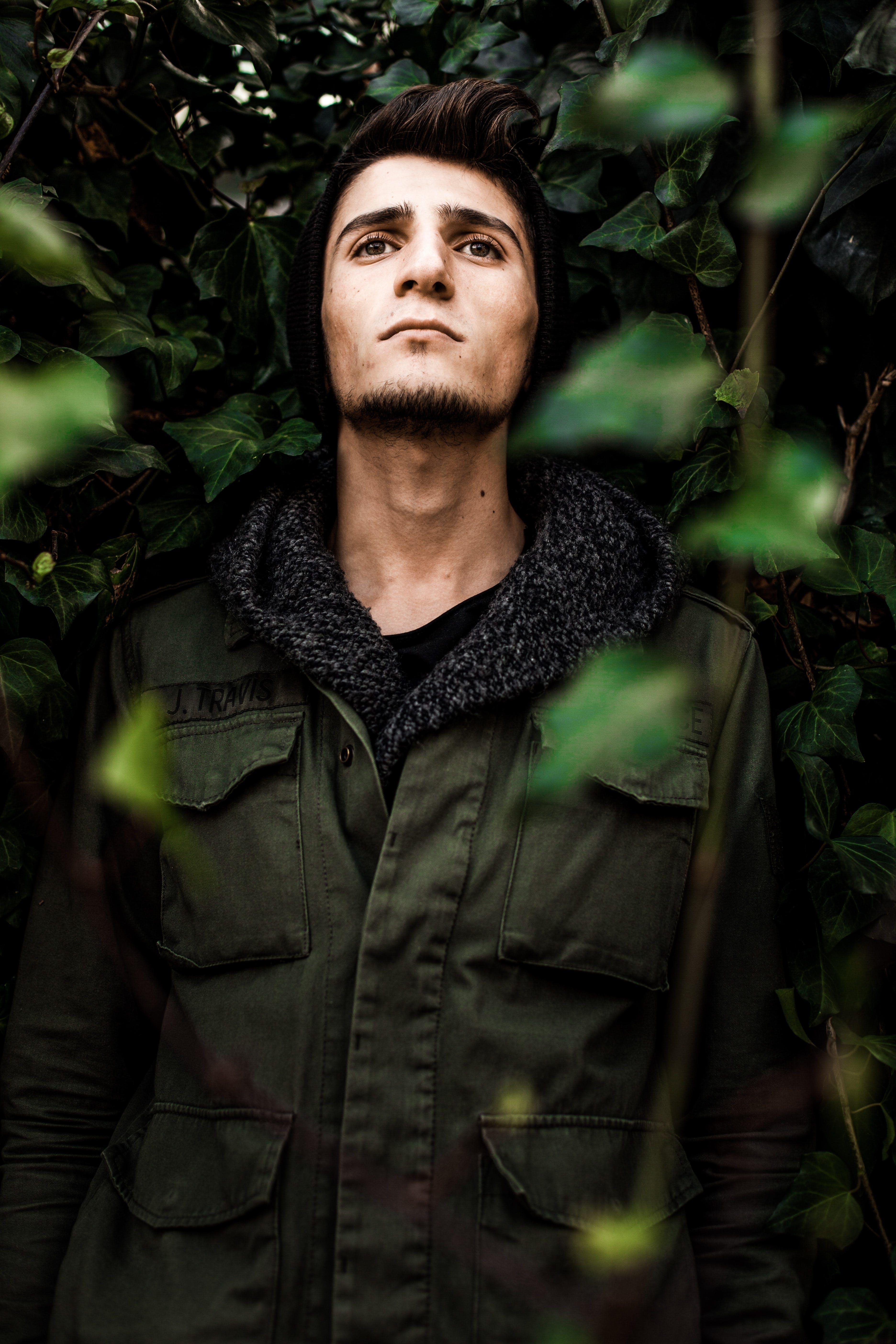 Man in Green Jacket Standing Outdoor