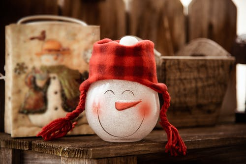 Snowman Glass Figurine on Brown Wooden Surface