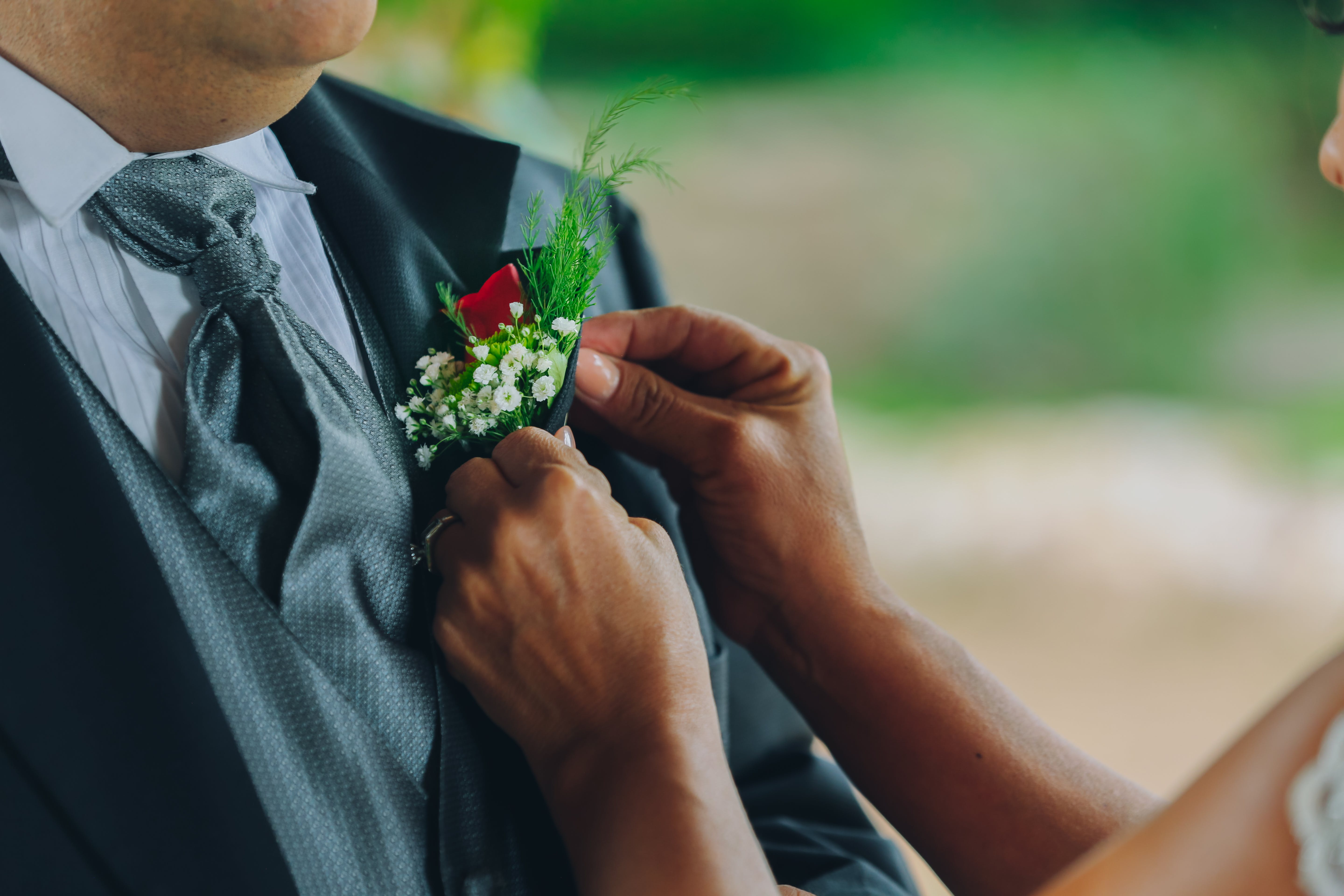 Woman Holding Man's White Boutonniere