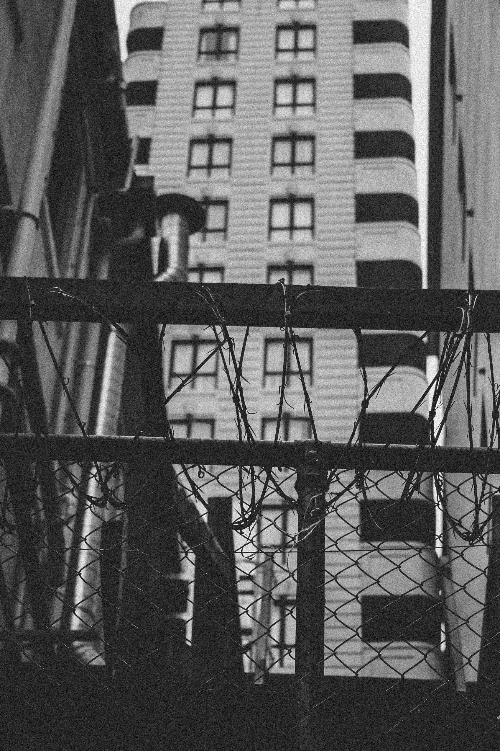 Grayscale Photography of Chain Link Fence Near Building