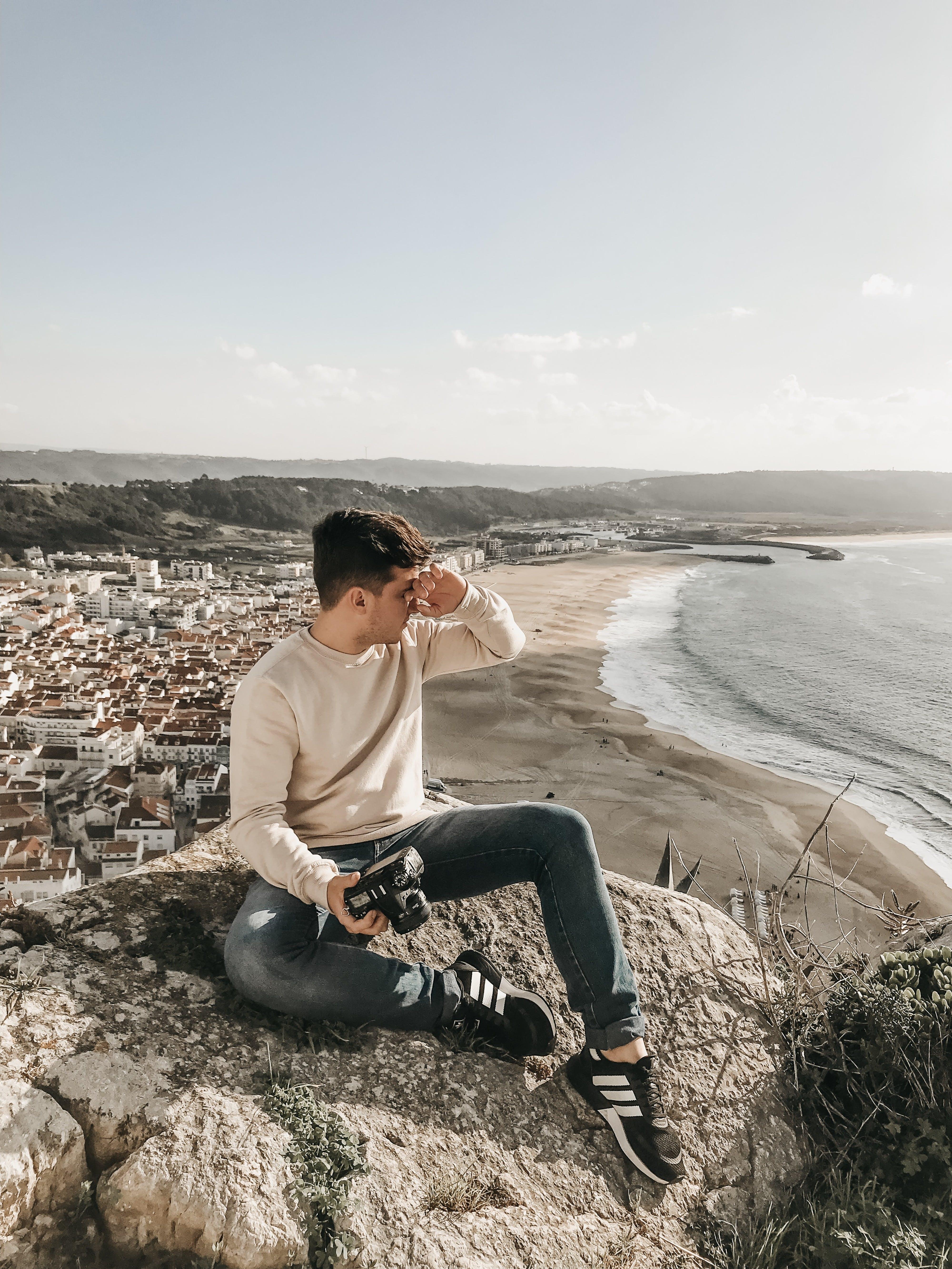 Photographer Holding DSLR Camera Sitting on a Huge Rock