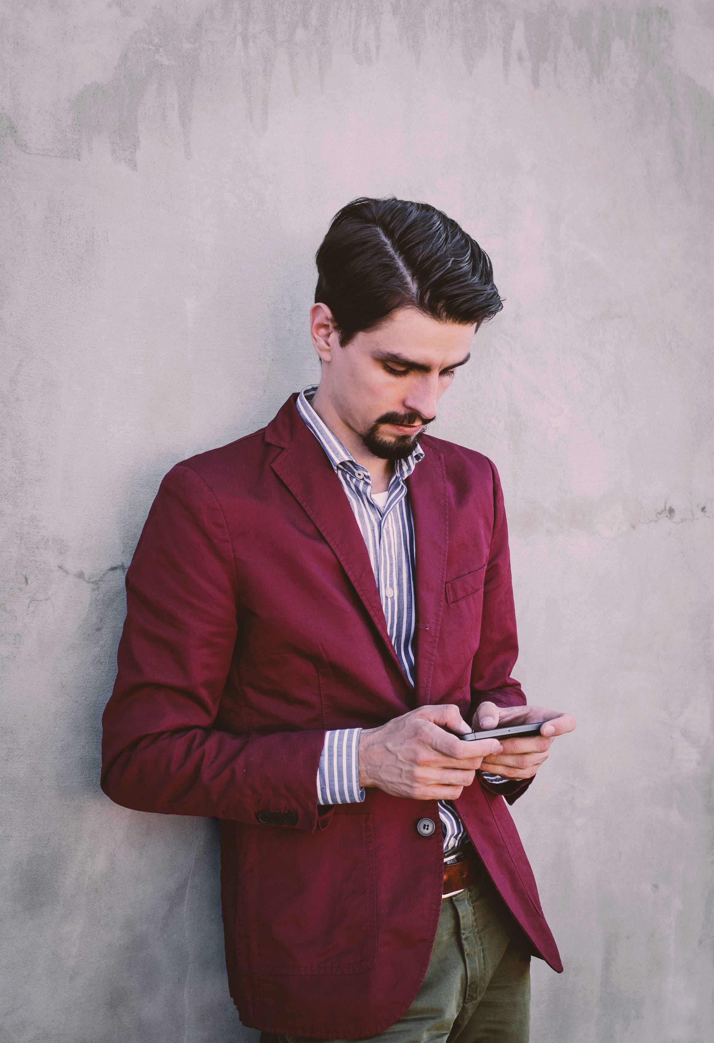Man Wearing Maroon Blazer Leaning on Gray Concrete Wall While Using His Smartphone