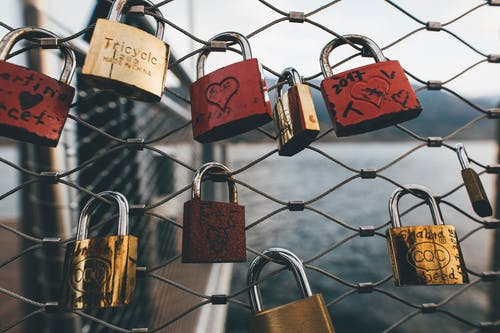 Red and Brown Padlock on Chain Link Fence