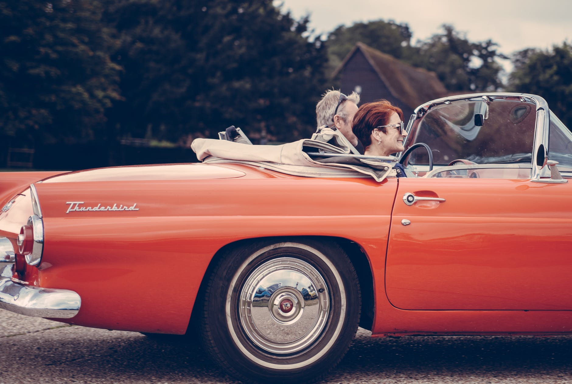old couple riding a vintage ford thunderbird