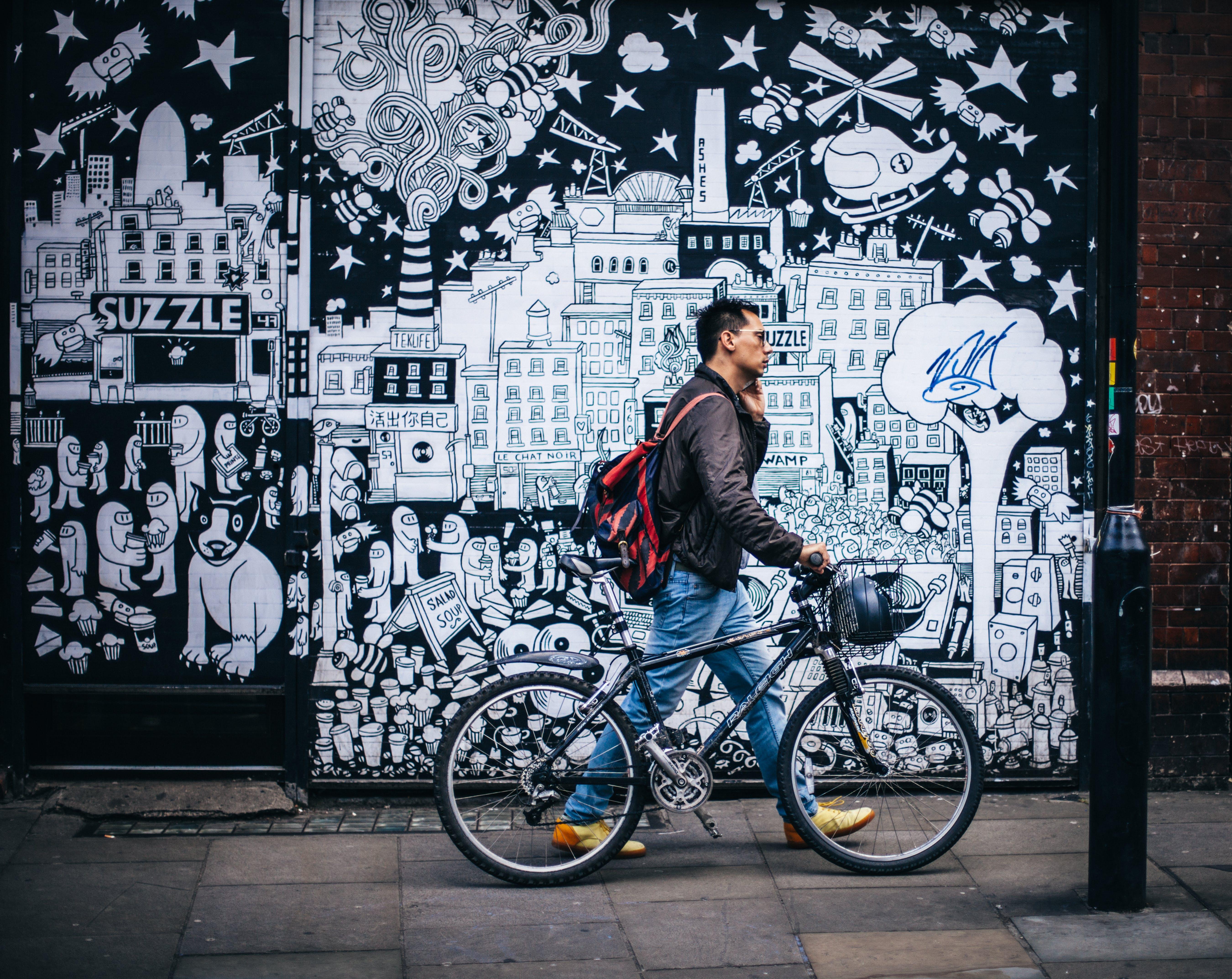 Man in Black Jacket Holding a Black Hardtail Bike Near Black and White Art Wall