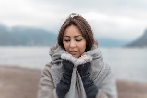 Selective Focus Photography of Woman Embracing Grey Blanket