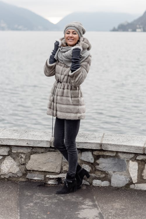 Smiling Woman Wearing Grey Hooded Coat Standing Beside Body Of Water