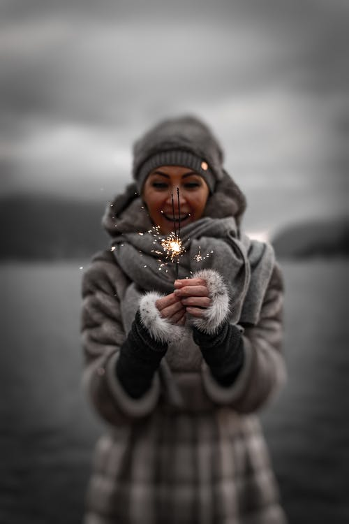 Photo of Smiling Woman in Winter Clothing Holding Sparklers