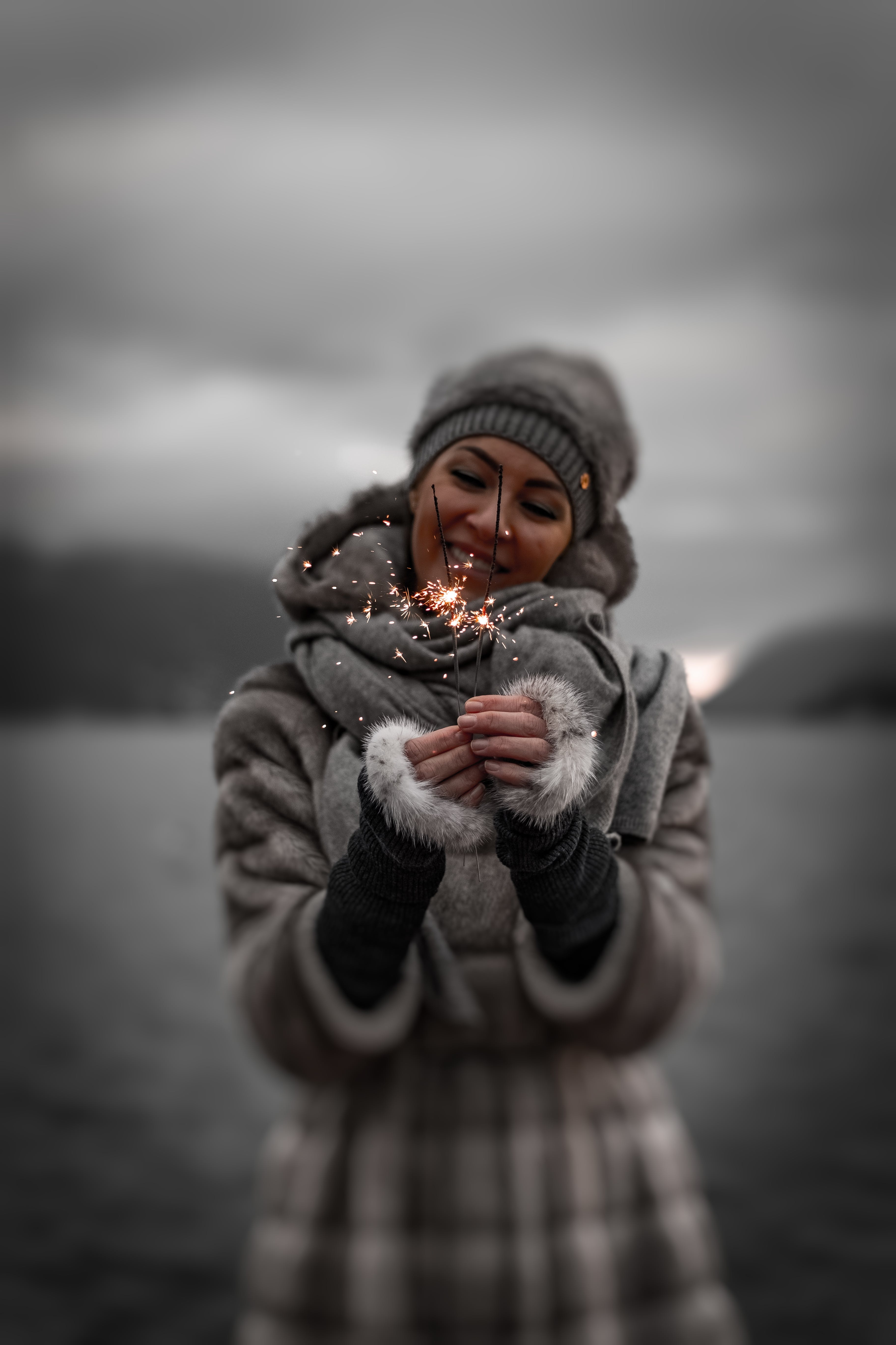Photo of Smiling Woman Holding Lit Sparklers
