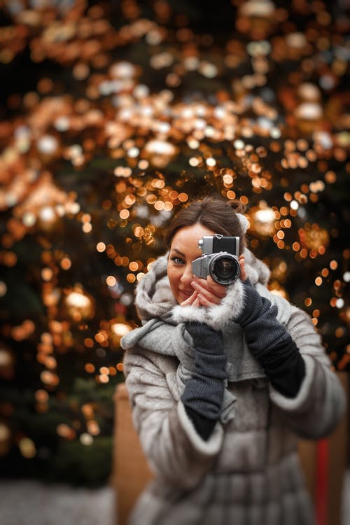 Photo of Woman in Winter Coat Taking a Photo