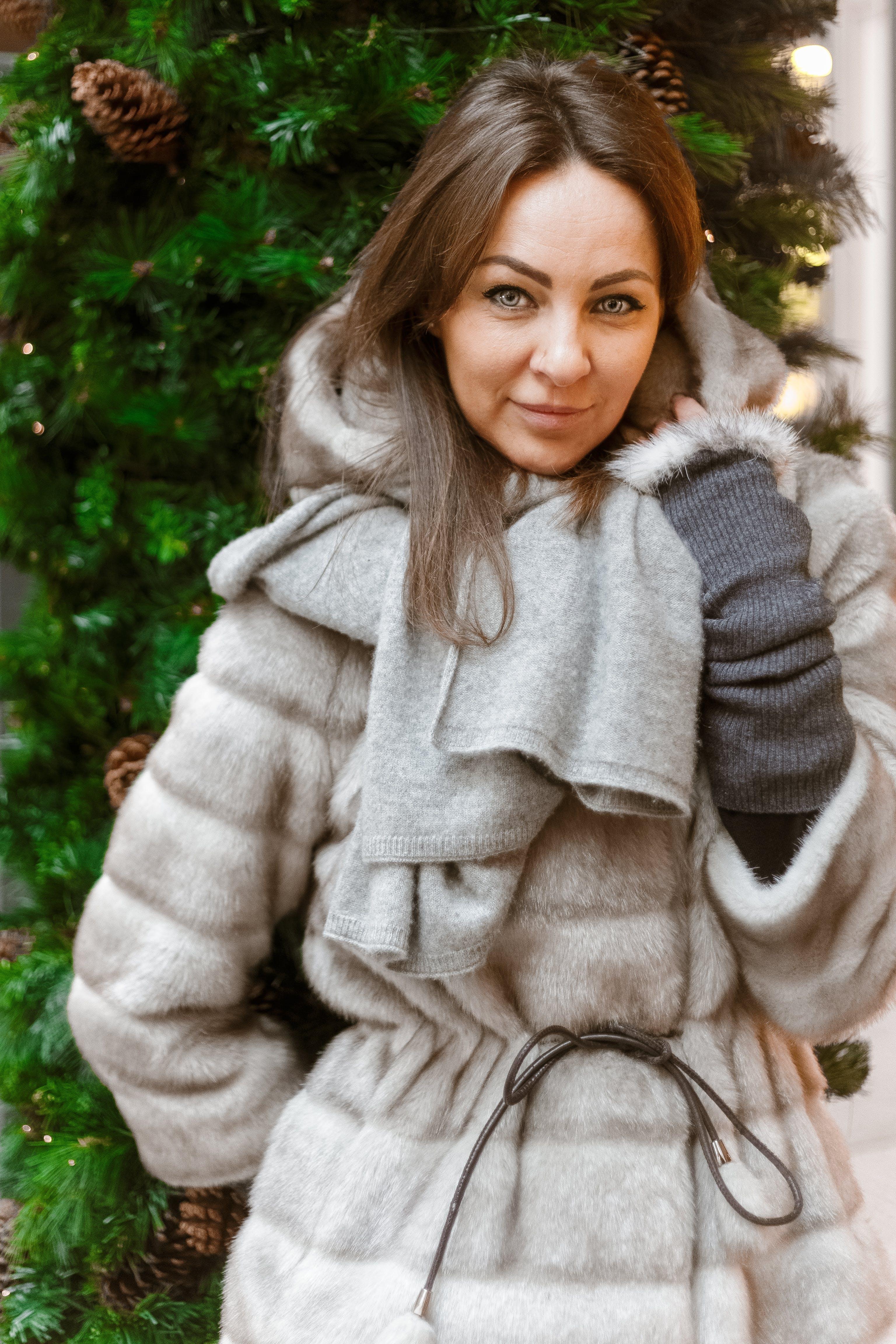 Woman in Winter Coat Standing Near Christmas Tree