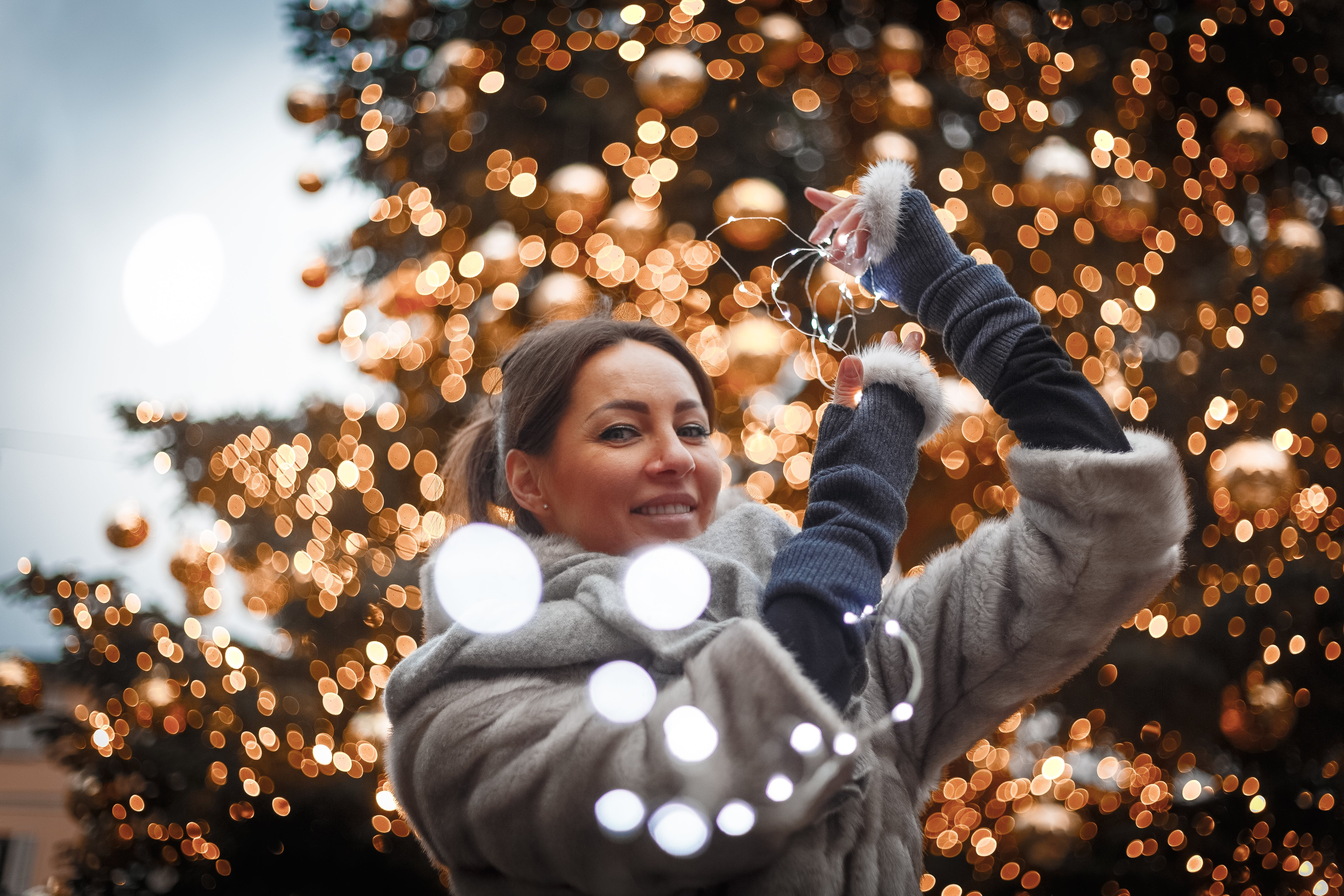 Selective Focus Photo of Woman Holding String Lights