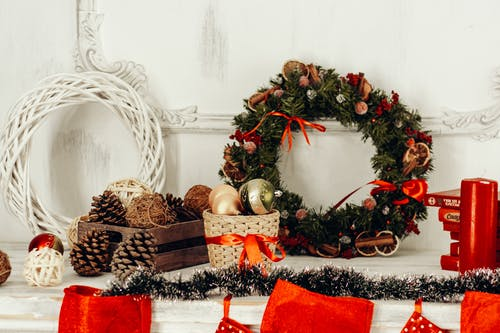 Pine Cones and Christmas Wreaths Placed on White Table