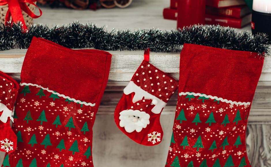 three red and green christmas stocking mounted on wall free stock