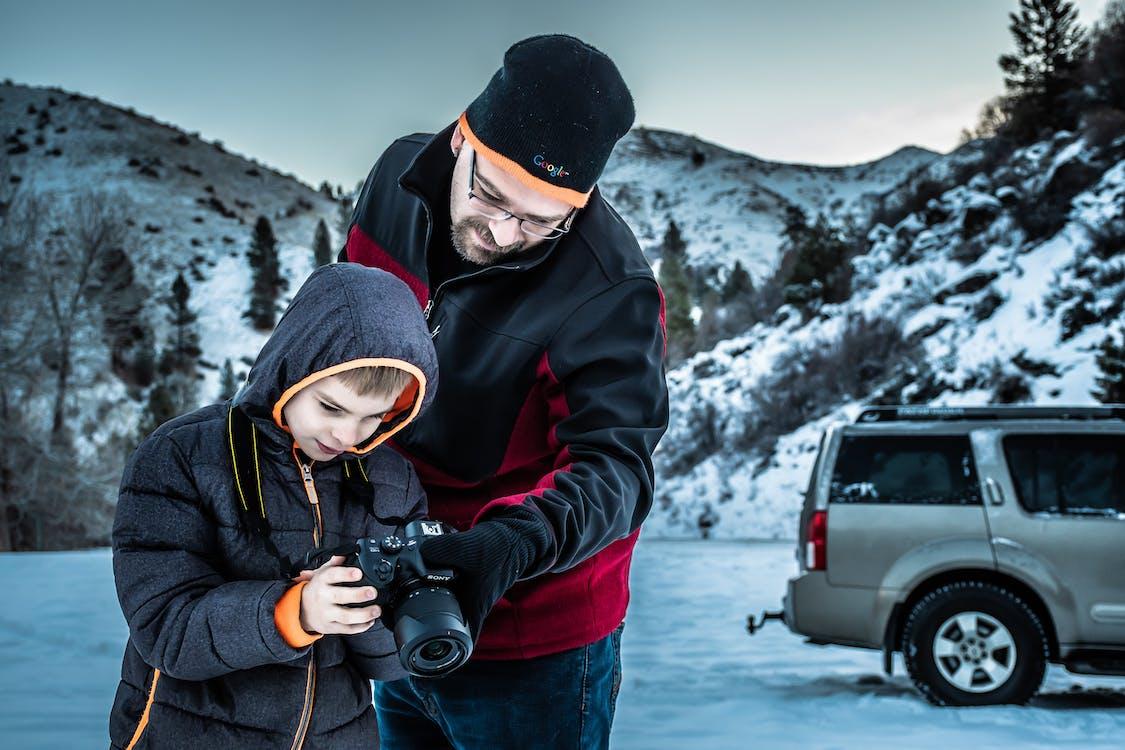 Man and Boy Looking at Dslr Camera
