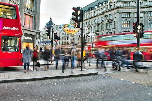 Ilmainen kuvapankkikuva tunnisteilla bussit, epäselvä liike, jalankulkijat, katukyltti