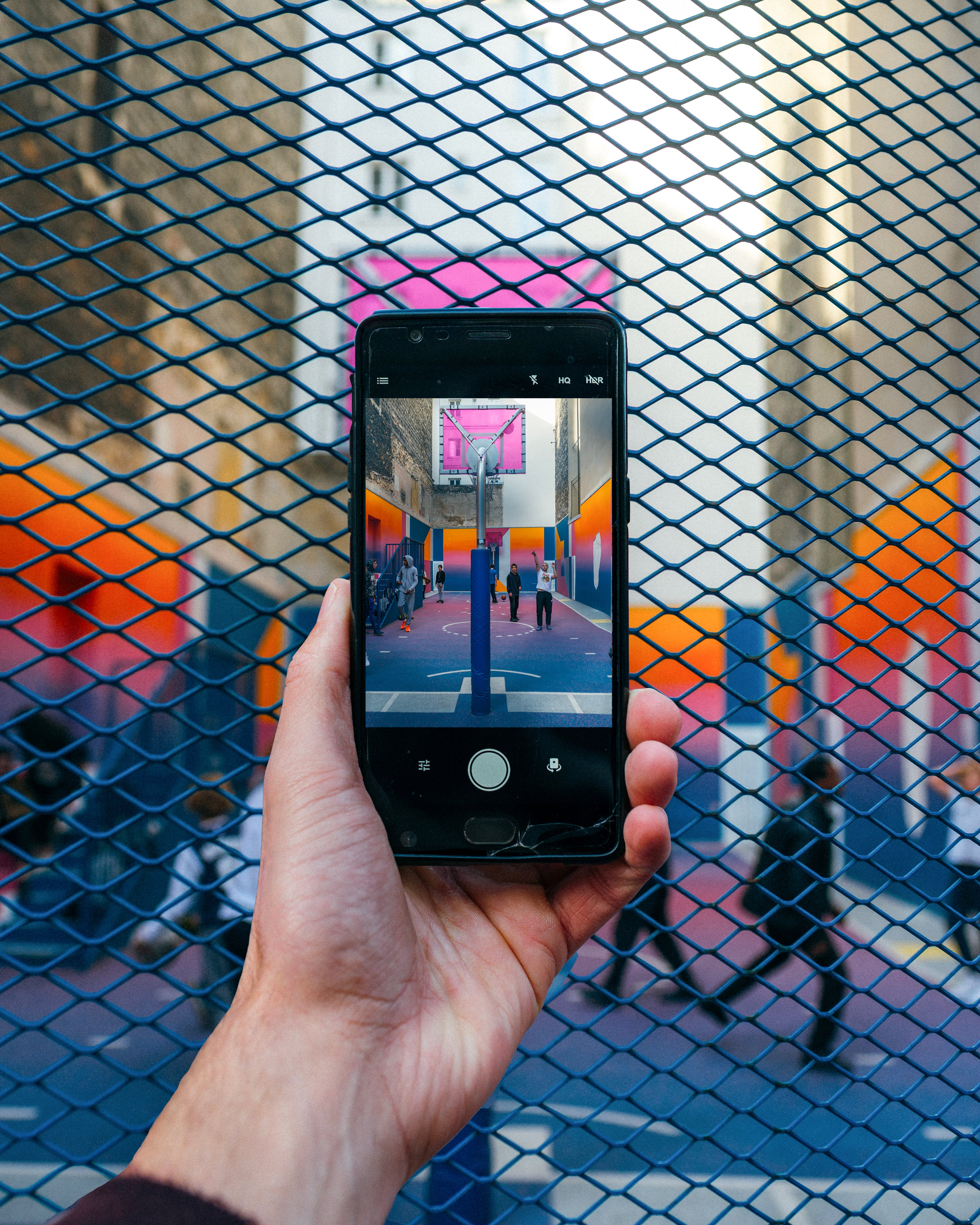 Person Taking Photo Of People In Basketball Court
