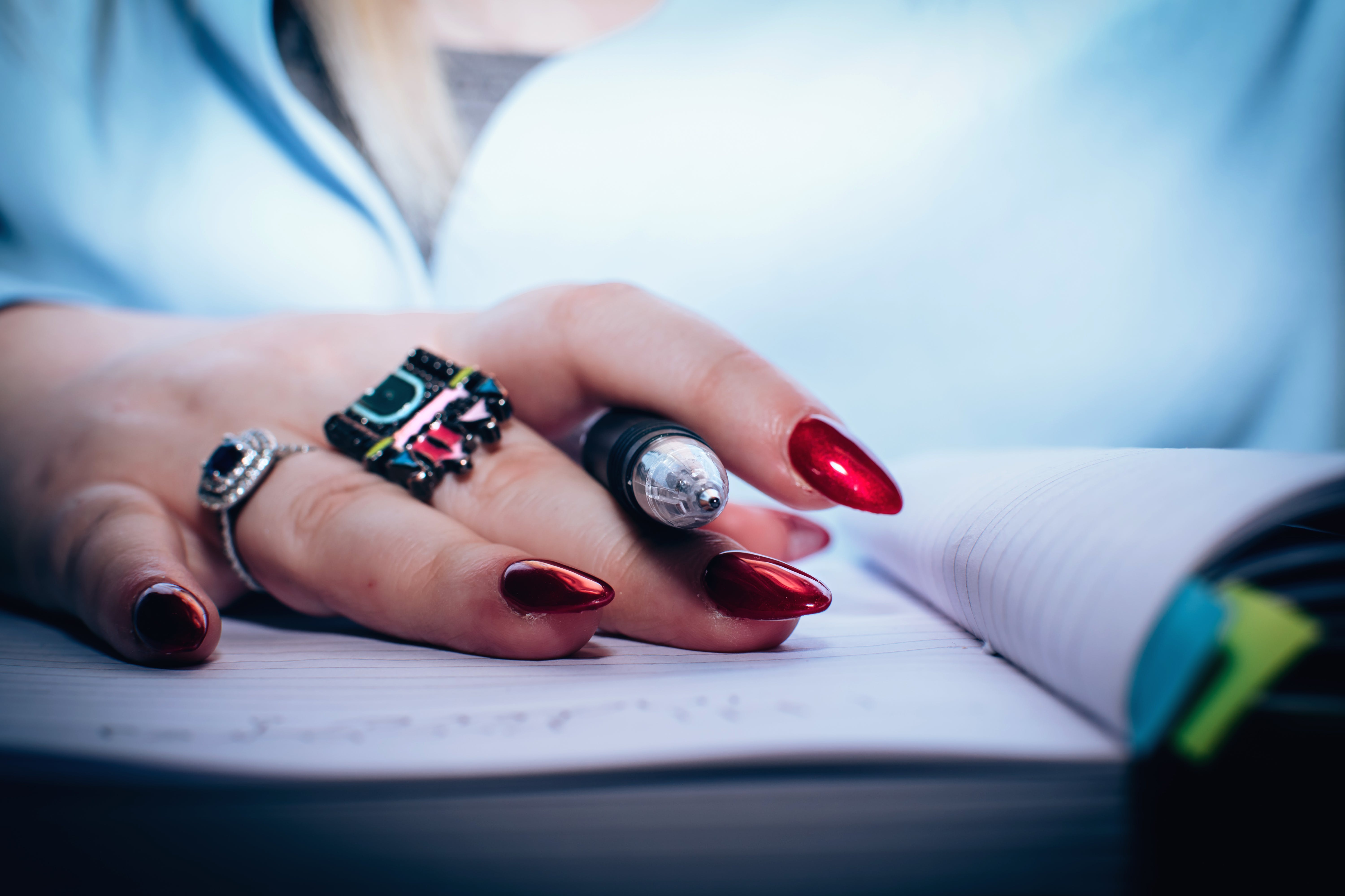 Person With Red Nail Polish Holding Black Pen